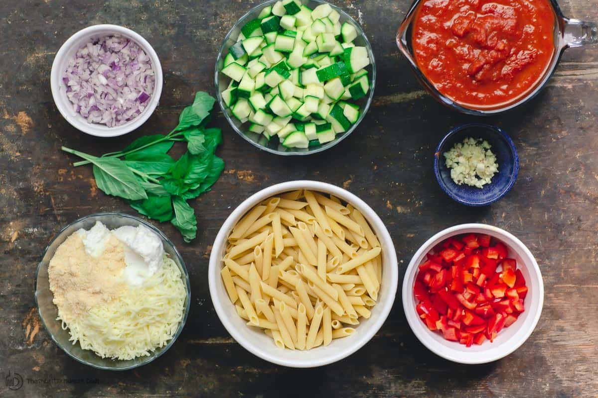 Ingredients for vegetarian baked ziti. Pasta, vegetables, sauce, and ricotta cheese mixture