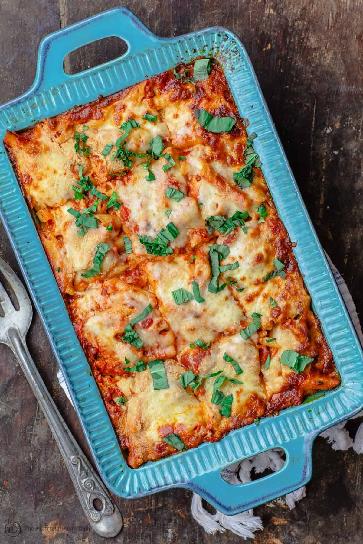 Vegetarian Baked Ziti in Blue Casserole Dish. Serving spoon on the side