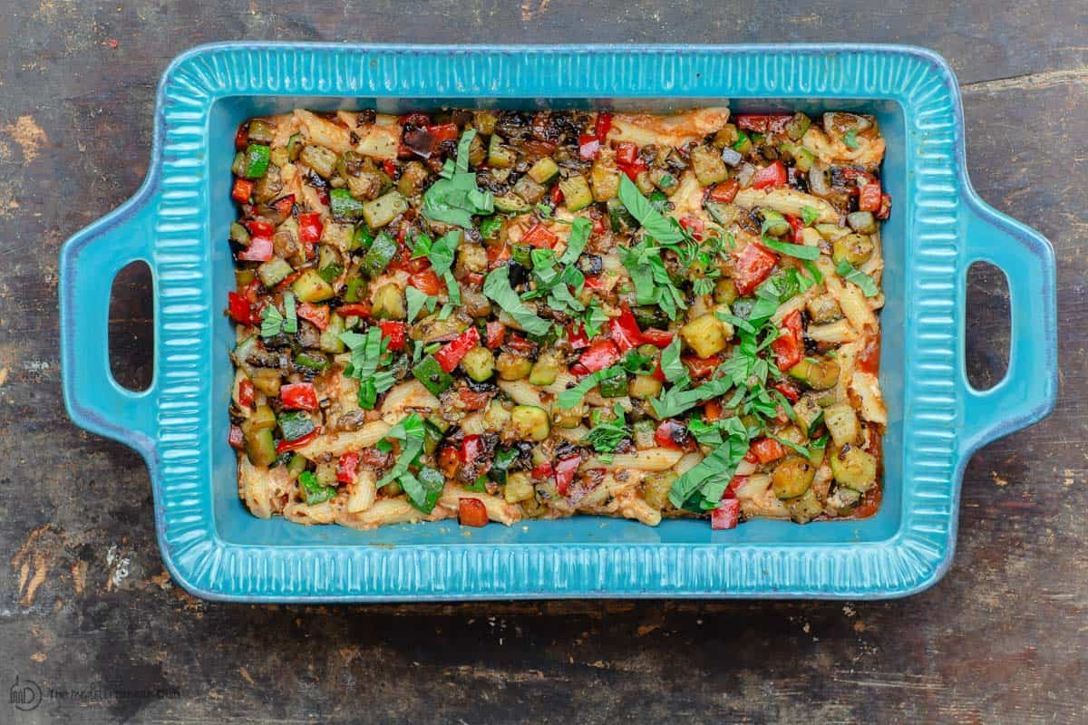 Layer of vegetables on top of pasta in casserole dish
