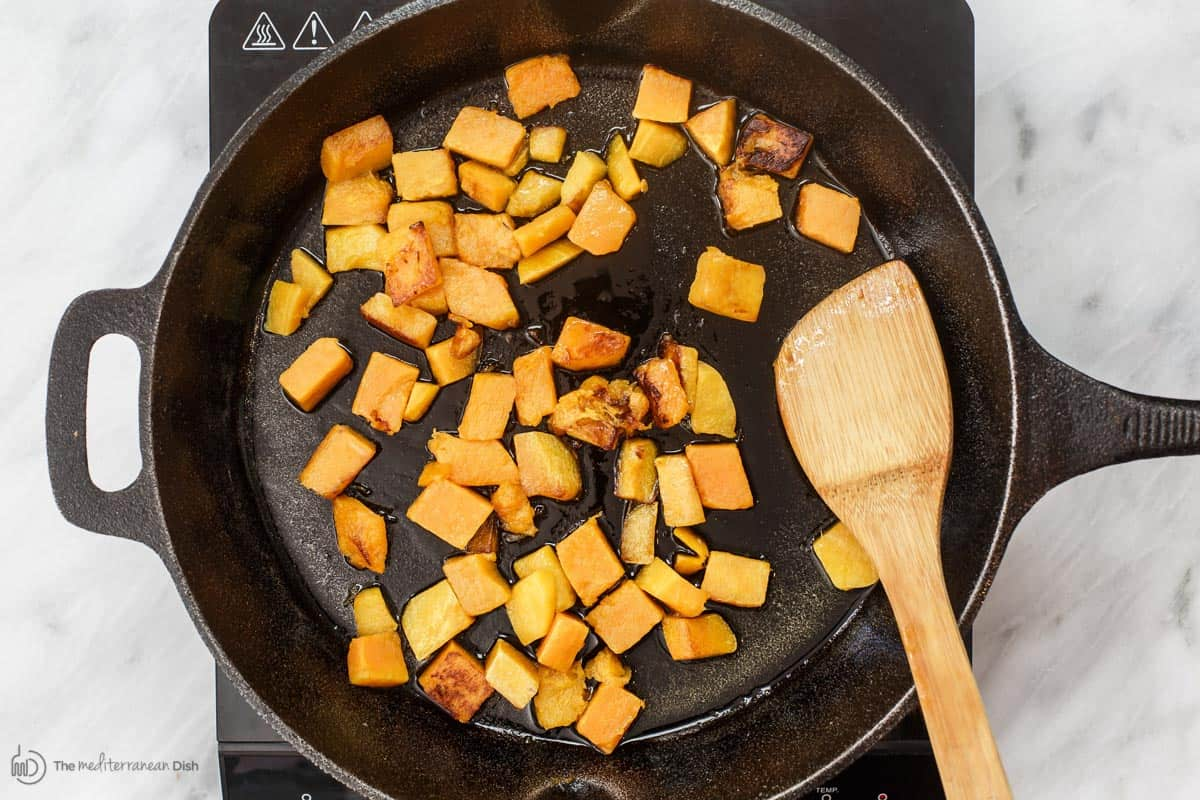 Butternut squash cubes cooking in pan