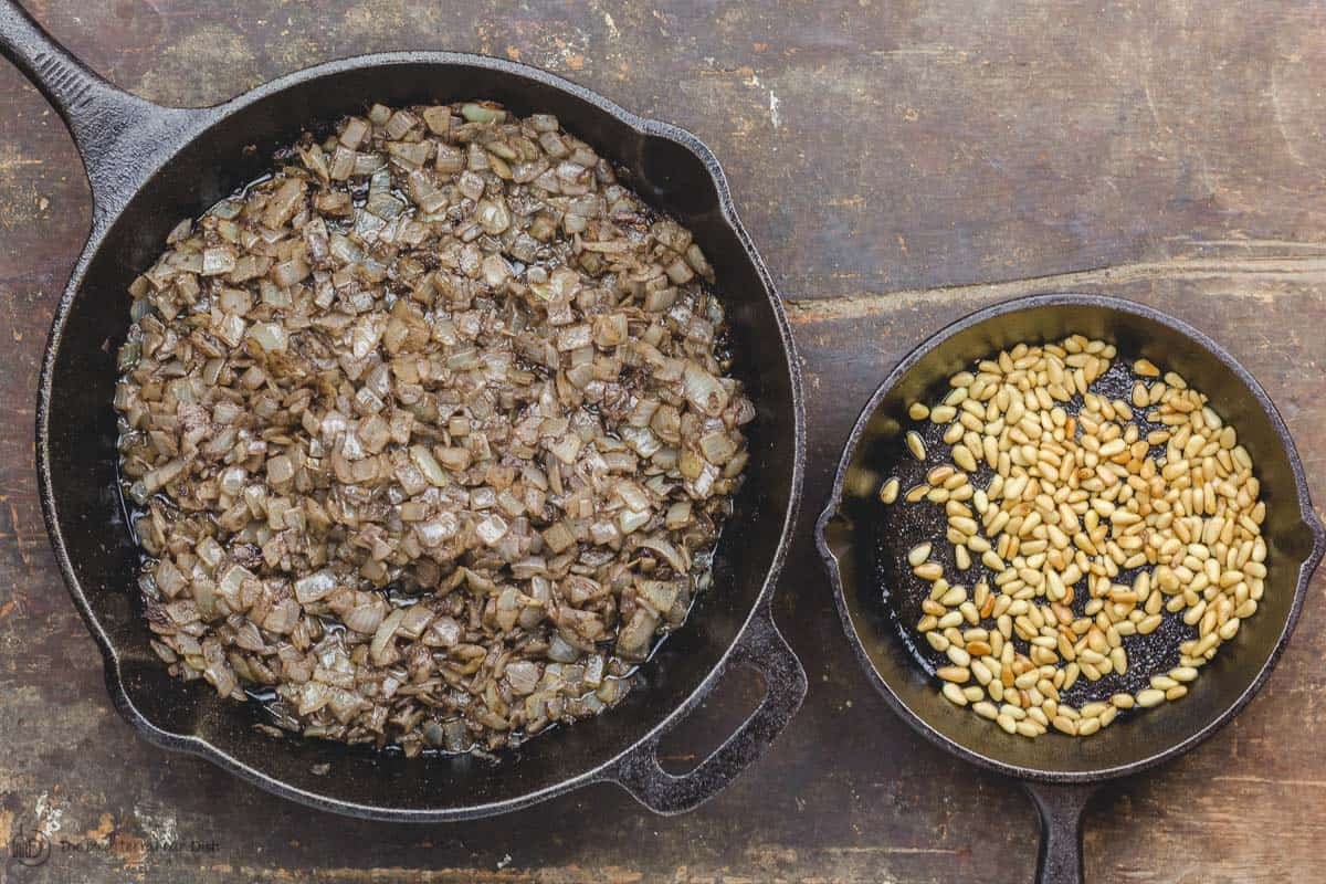 Cooked onions and roasted pine nuts in two skillets