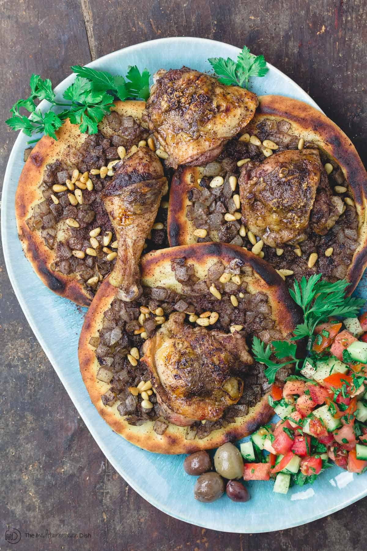 Musakhan sumac chicken over carmalized onion flatbread with side salad