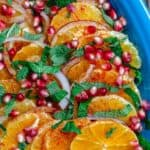 Orange Salad arranged on platter with pomegranate seeds, fresh mint, and onions