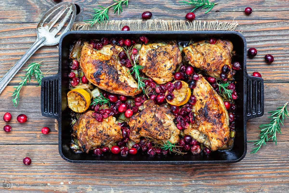 Finished baked cranberry chicken in pan, serving spatula to the side