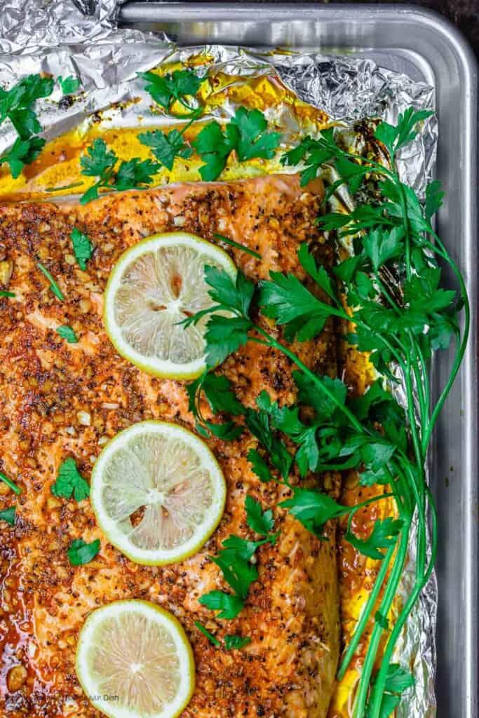 Lemon Garlic Salmon on Baking Sheet with Parsley Garnish and lemon slices