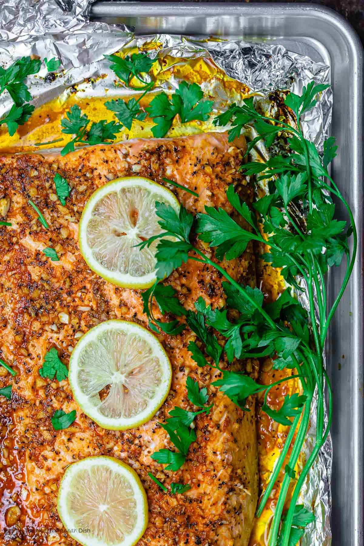 Lemon Garlic Salmon on Baking Sheet with Parsley Garnish and lemon slices
