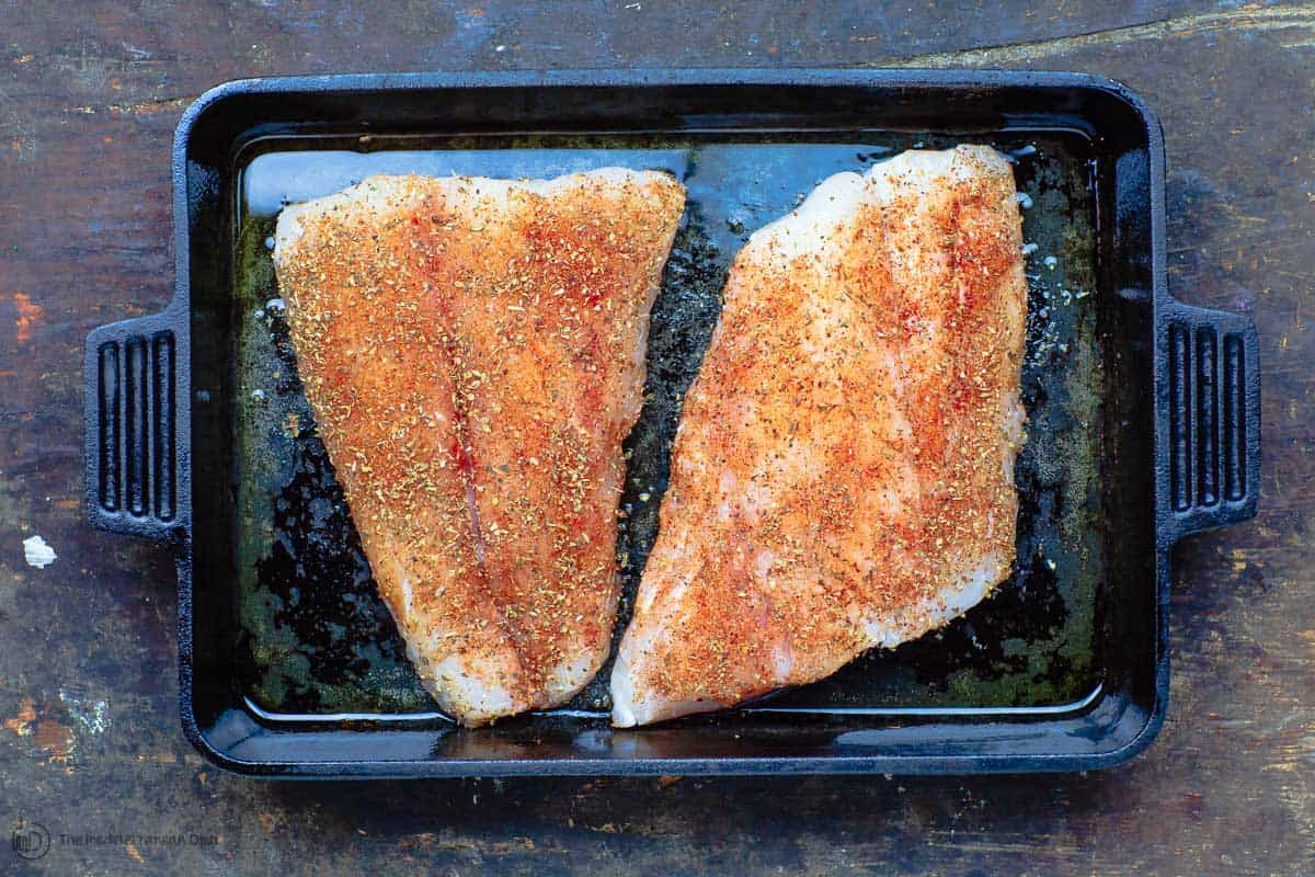 Fish fillets seasoned with spices and placed on baking pan