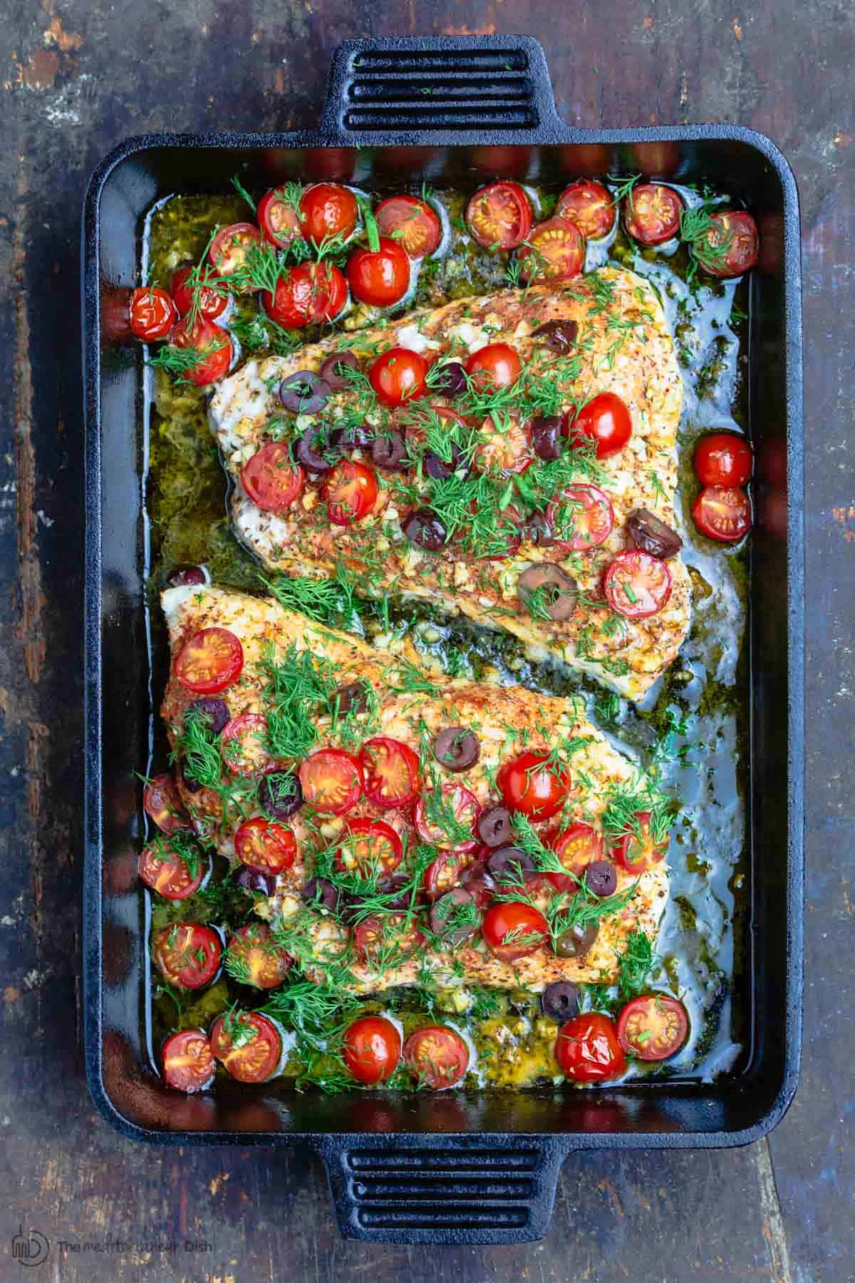 Baked grouper in black baking pan, topped with tomatoes, olives and fresh dill