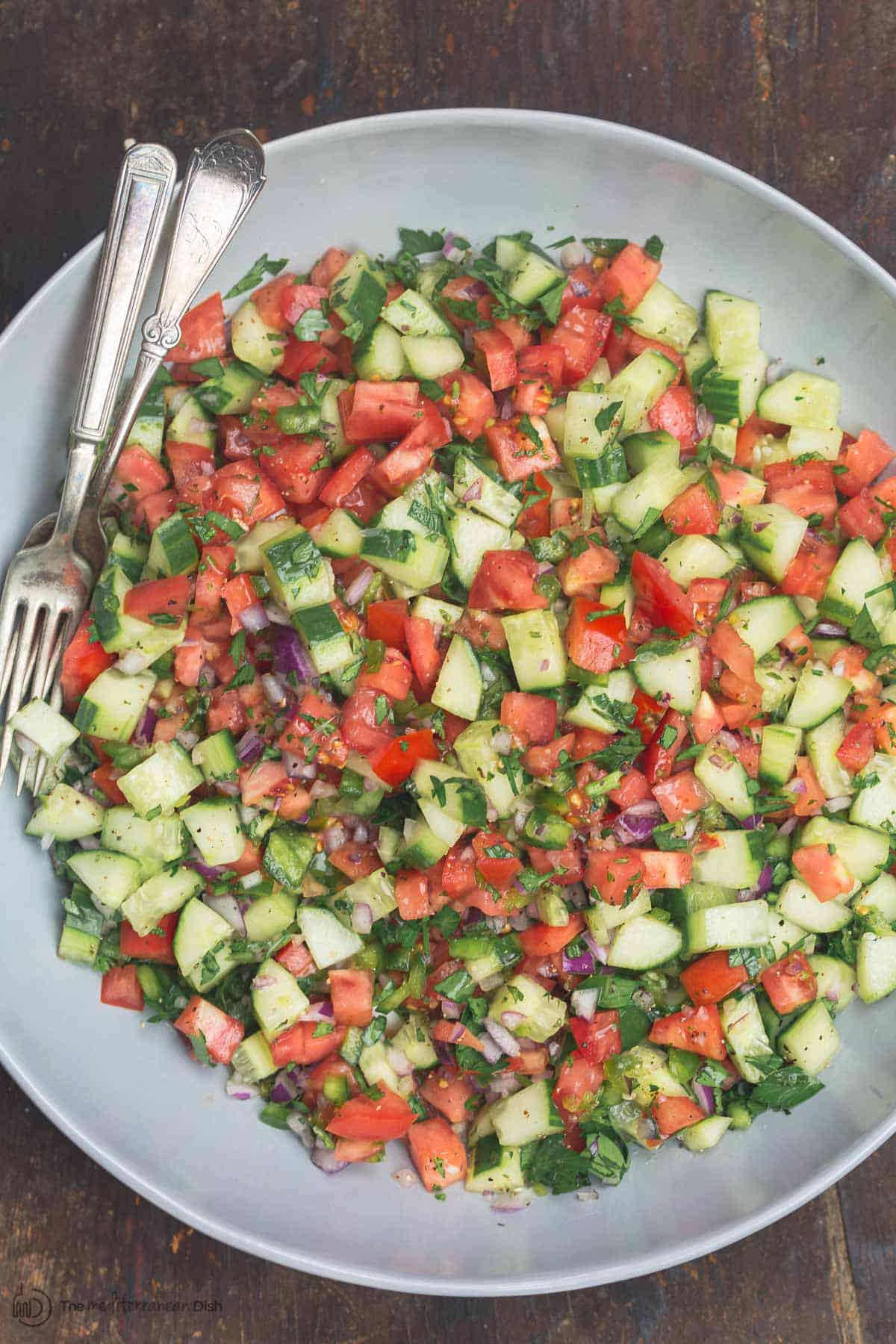 Mixed shiarzi salad with cucumbers, tomatoes, bell peppers, onions, and fresh herbs