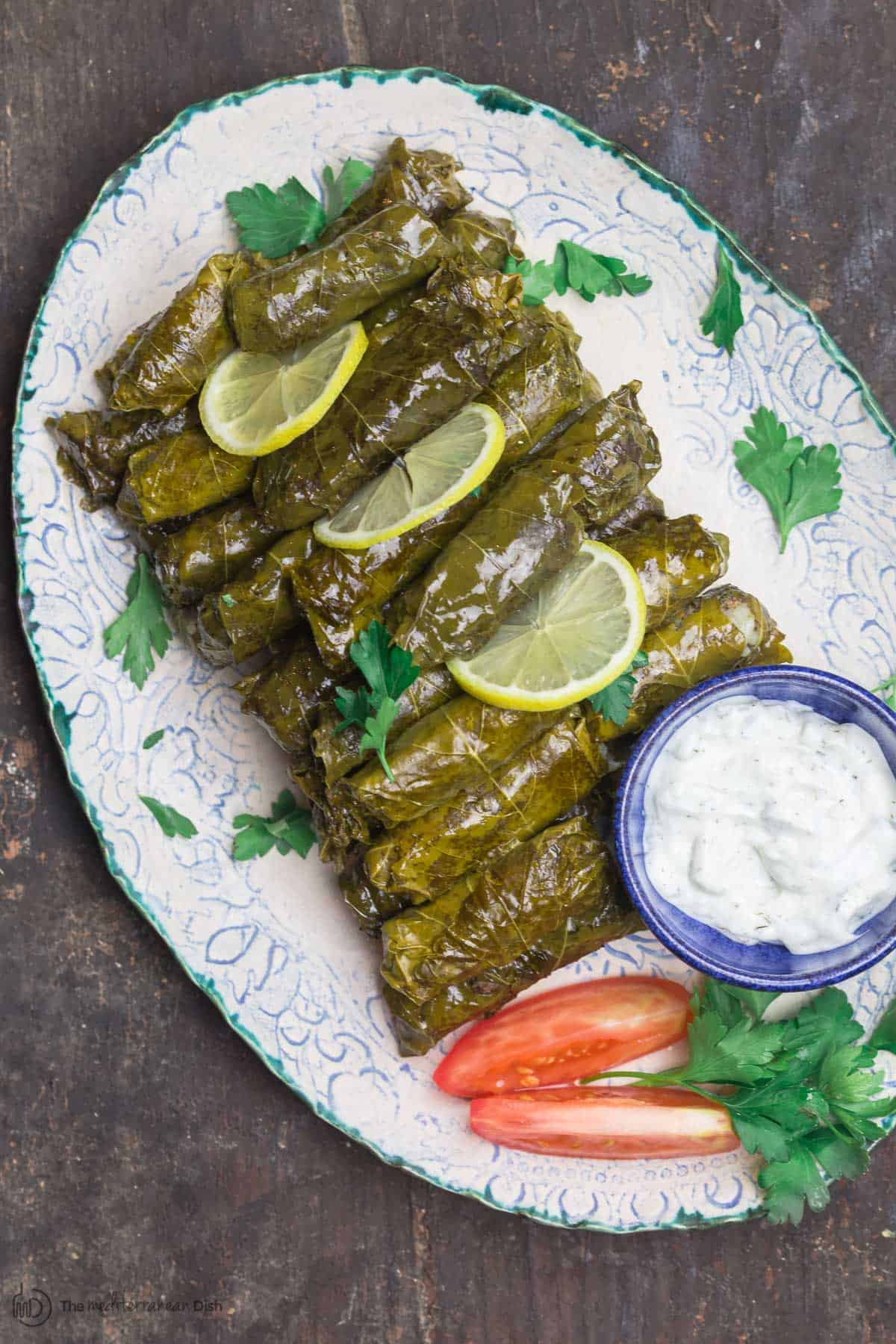 Stuffed Grape Leaves (Dolmas) on serving platter with tztaziki sauce and sliced tomatoes