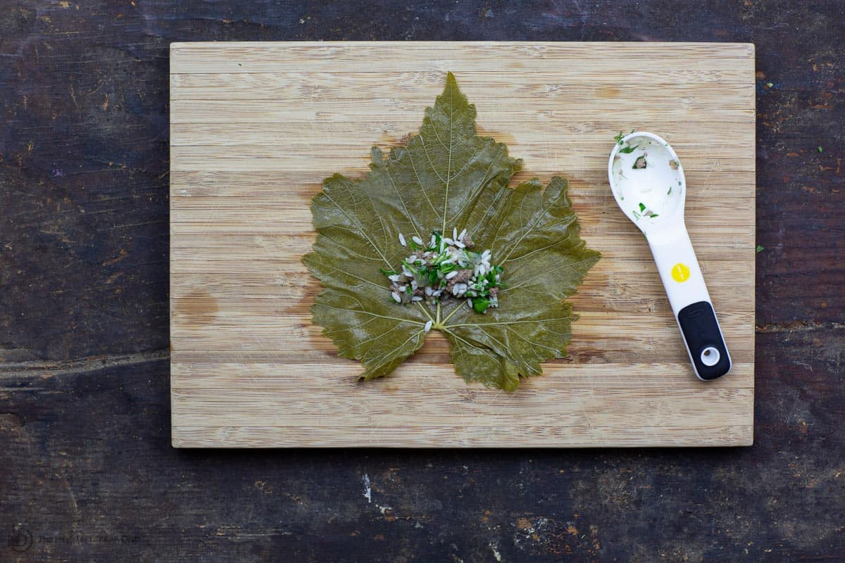 One grape leaf on cutting board with rice stuffing in middle