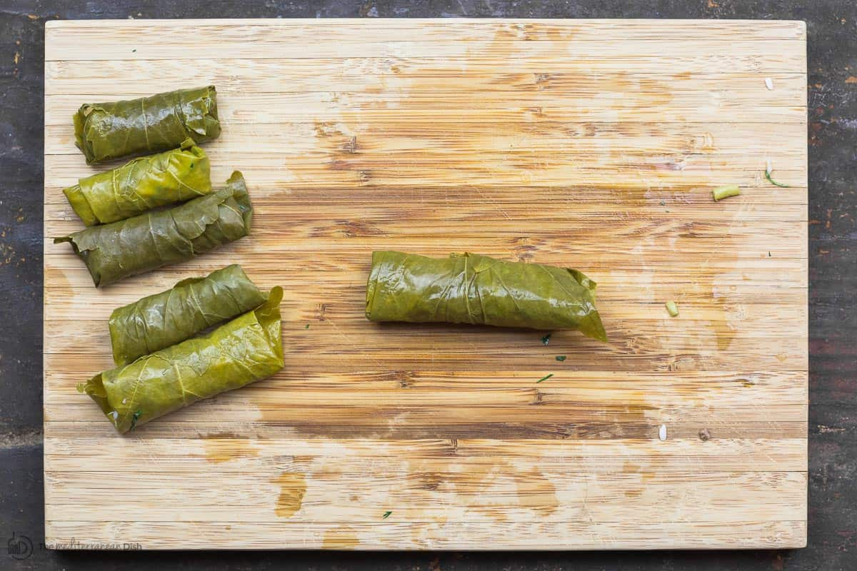 A few fully rolled stuffed grape leaves on cutting board