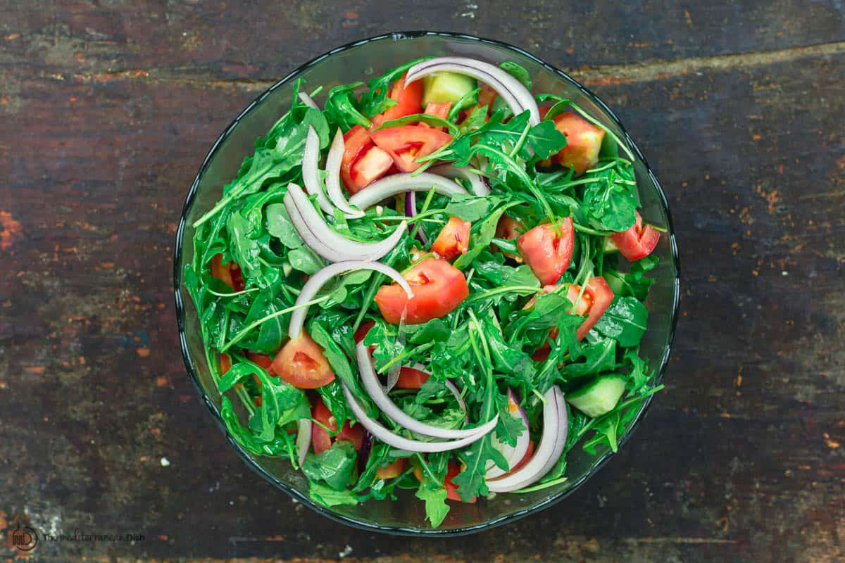 Arugula salad with tomatoes, cucumbers, and onions