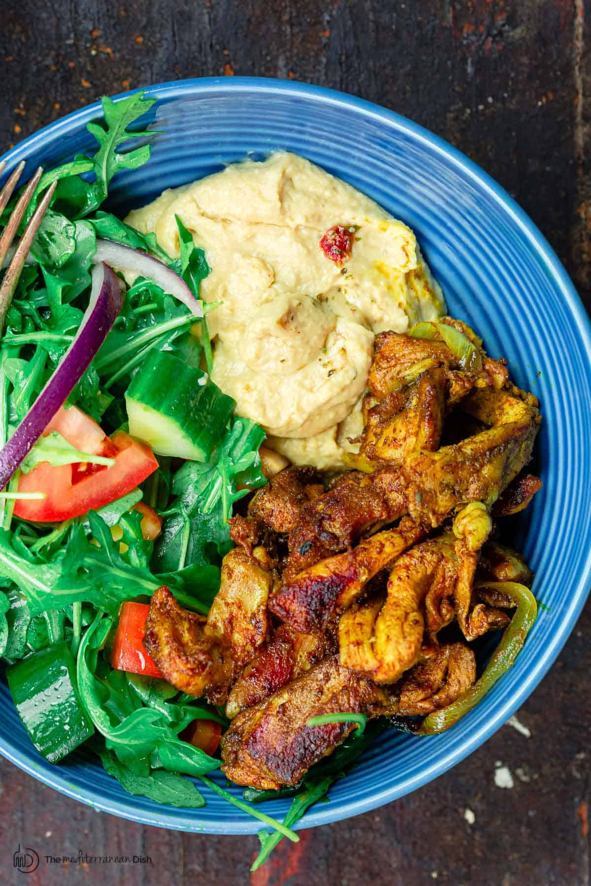 Chicken Shawarma Salad with arugula, tomatoes, and a side of hummus