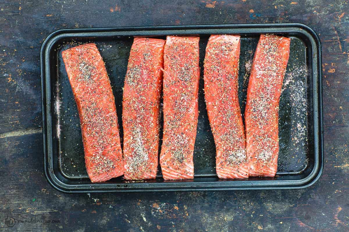 Raw salmon fillets seasoned and ready for searing