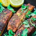 crispy pan seared salmon in a cast iron pan with lemon halves and arugula