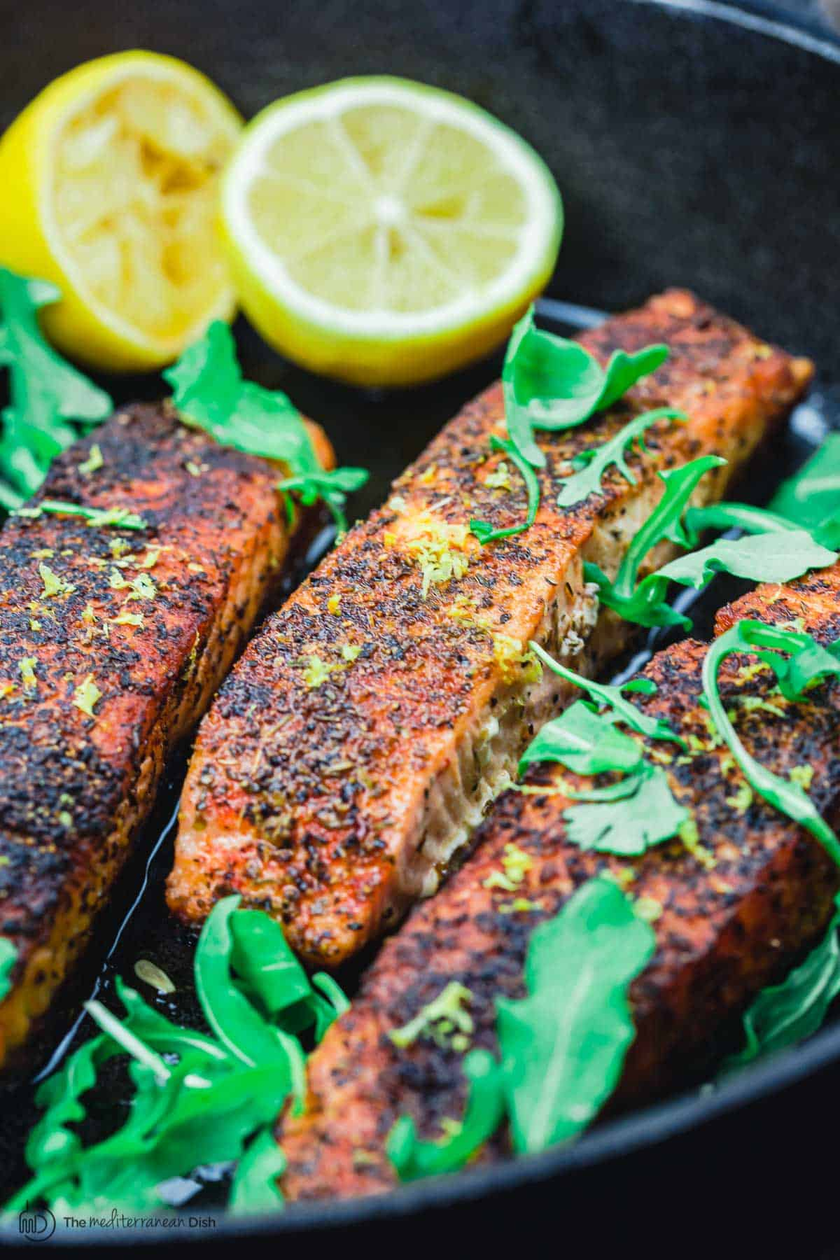 crispy pan seared salmon in a cast iron pan with lemon halves and arugula
