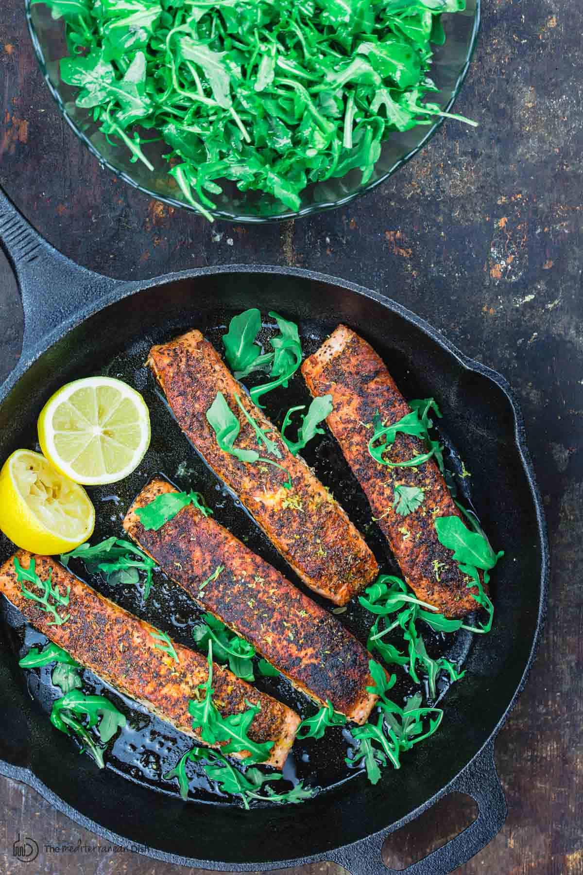 pan fried salmon in the pan and a side of arugula