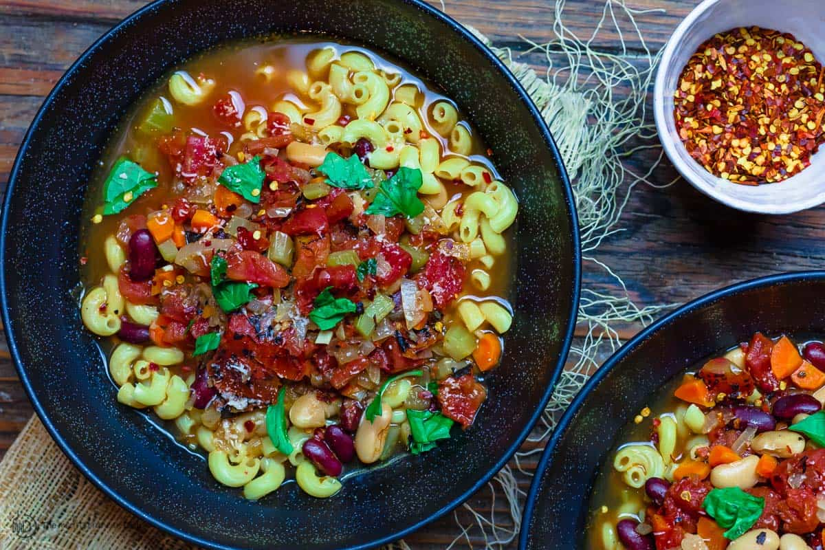 Pasta Fagioli dinner bowls, a side of crushed red pepper flakes