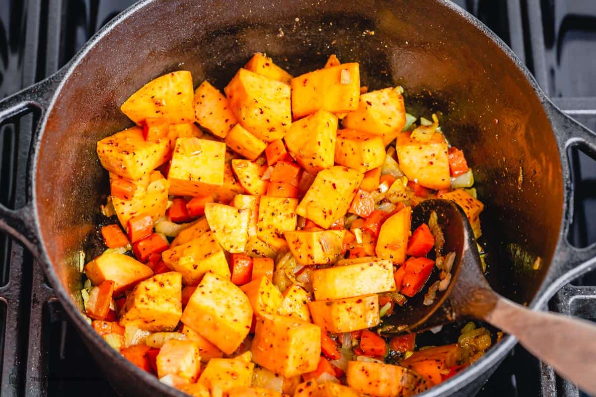 Sweet potatoes being sauteed with carrots, onions, and garlic