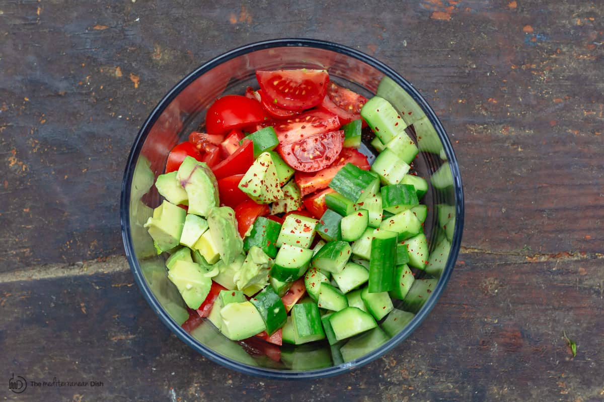 Avocados, tomatoes, and cucumbers in a bowl