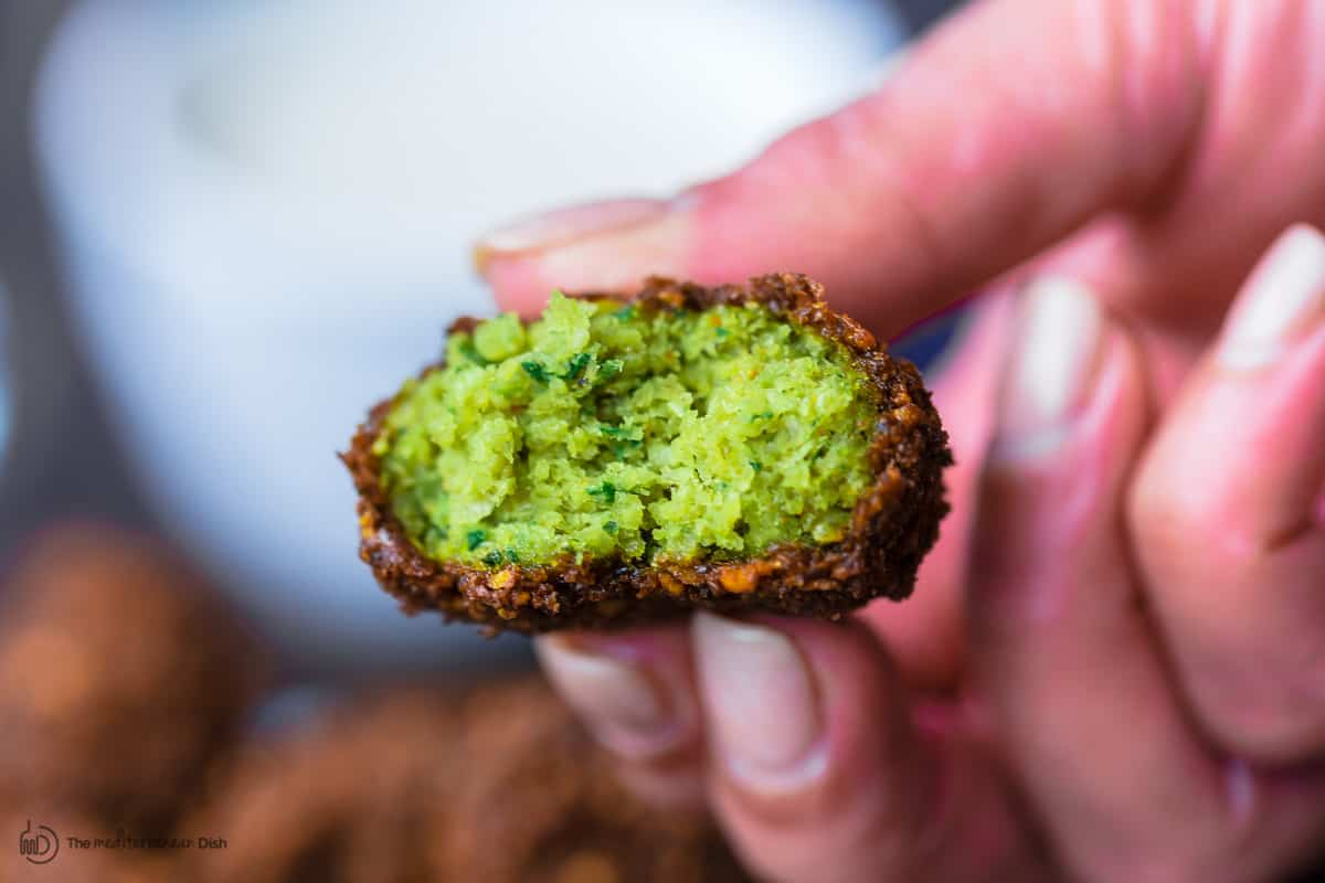 One falafel cut to reveal a green middle