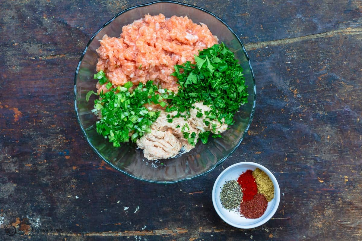 Salmon, fresh herbs, and spices in a bowl to form salmon burger mixture