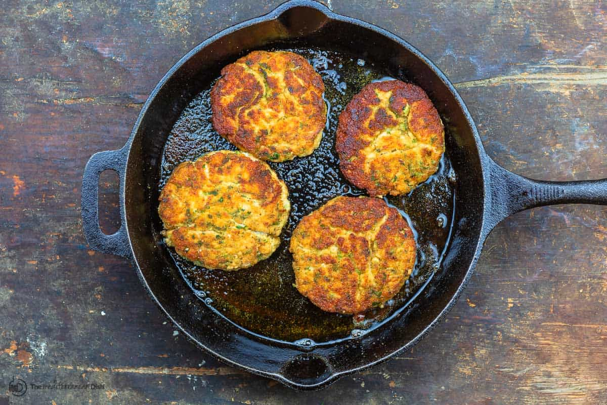 Cooked salmon burgers in skillet