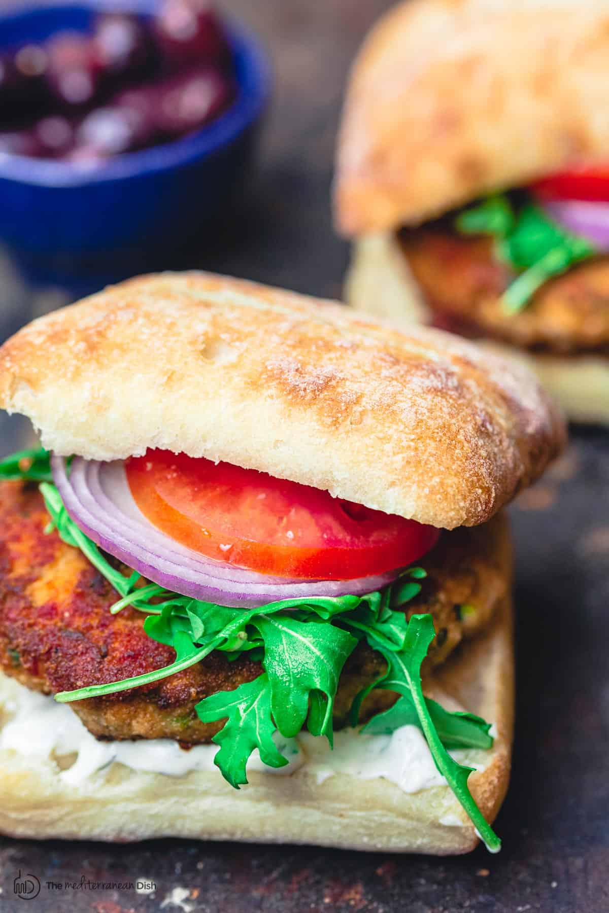 Juicy salmon burgers, served in Italian ciabatta rolls with arugula, tomatoes, and sliced onions
