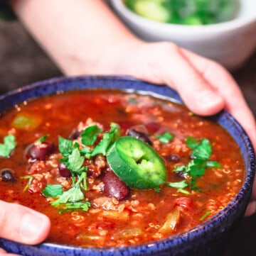 Bowl of vegan chili being held with a pair of hands