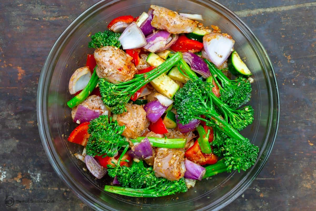 Chicken and vegetables in a bowl, tossed with garlic and spices and olive oil