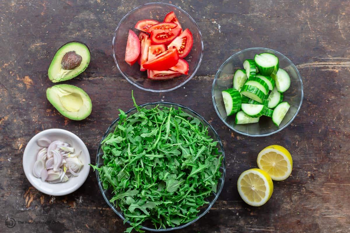Arugula salad ingredients. Arugula, cucumber, tomatoes, shallots, and avocado