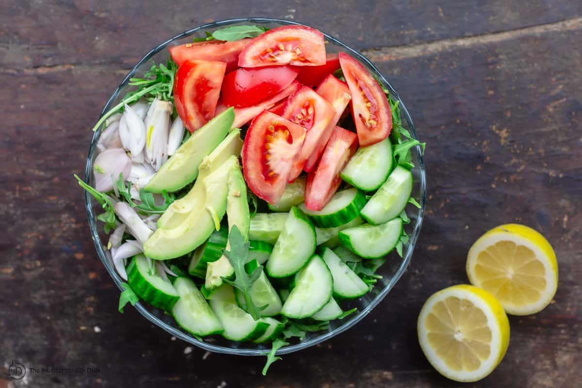 arugula salad in a large bowl with cucumbers, avocado, shallots and tomatoes. Lemons to the side