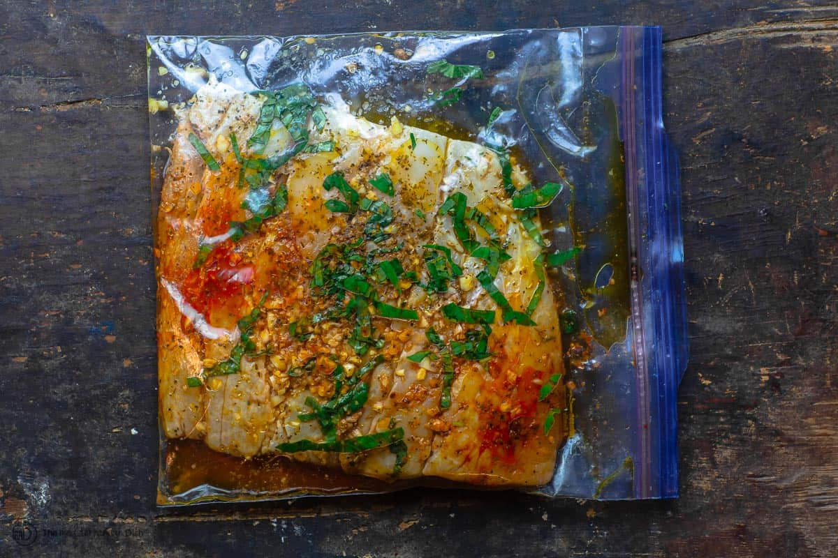 Fish fillet marinating in a large zip-top bag. Part of baked fish recipe