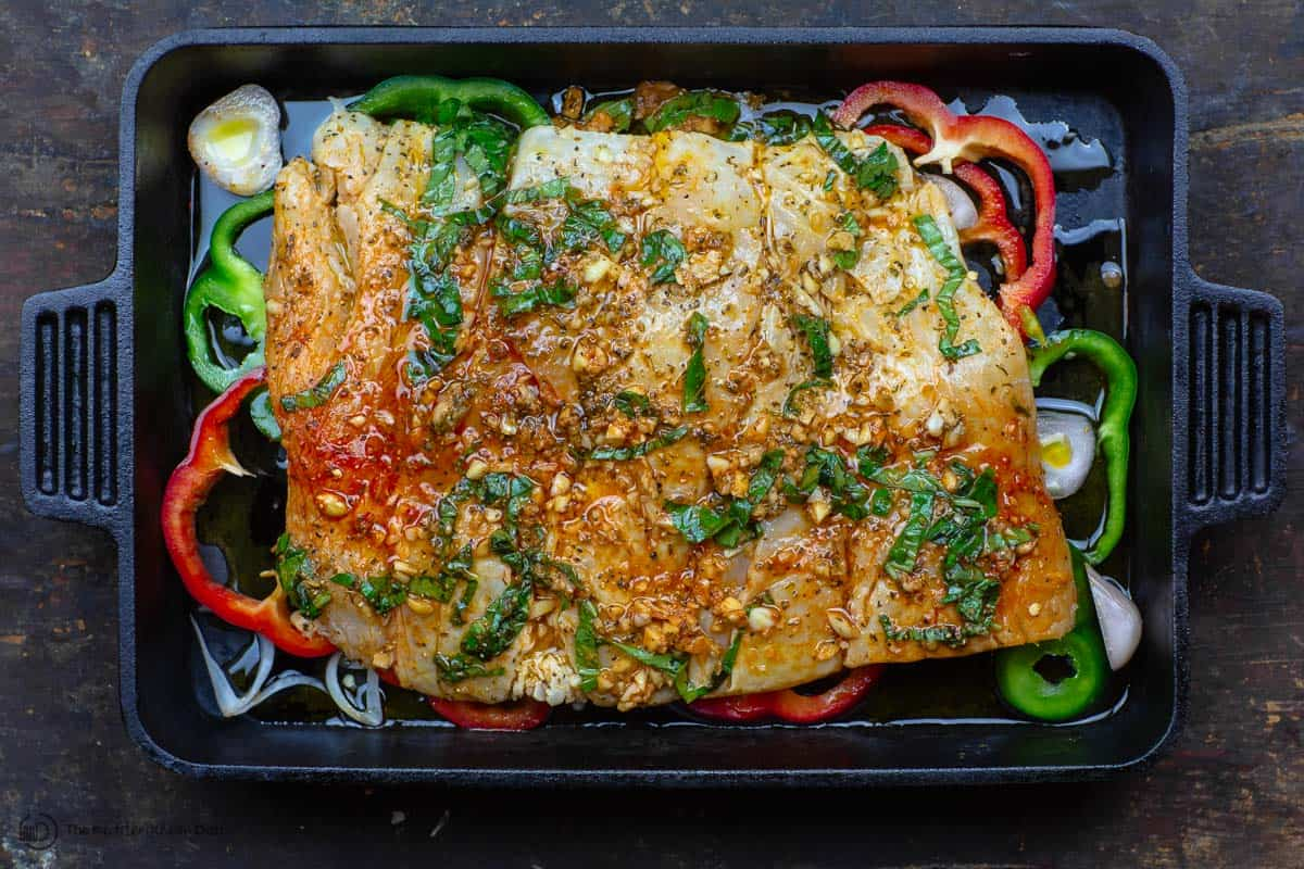Fish fillet placed in baking pan with marinade, shallots and bell peppers