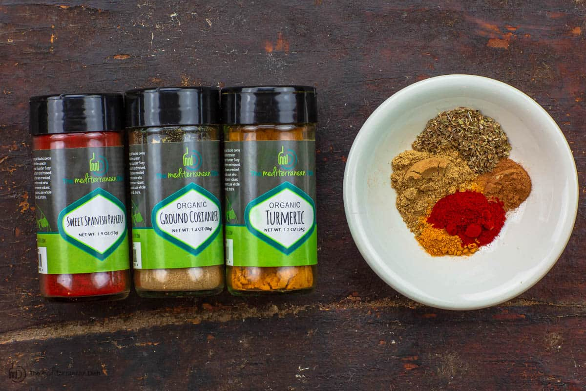 Spice bowl with paprika, coriander, oregano, turmeric, and black pepper. Three spice bottles to the side