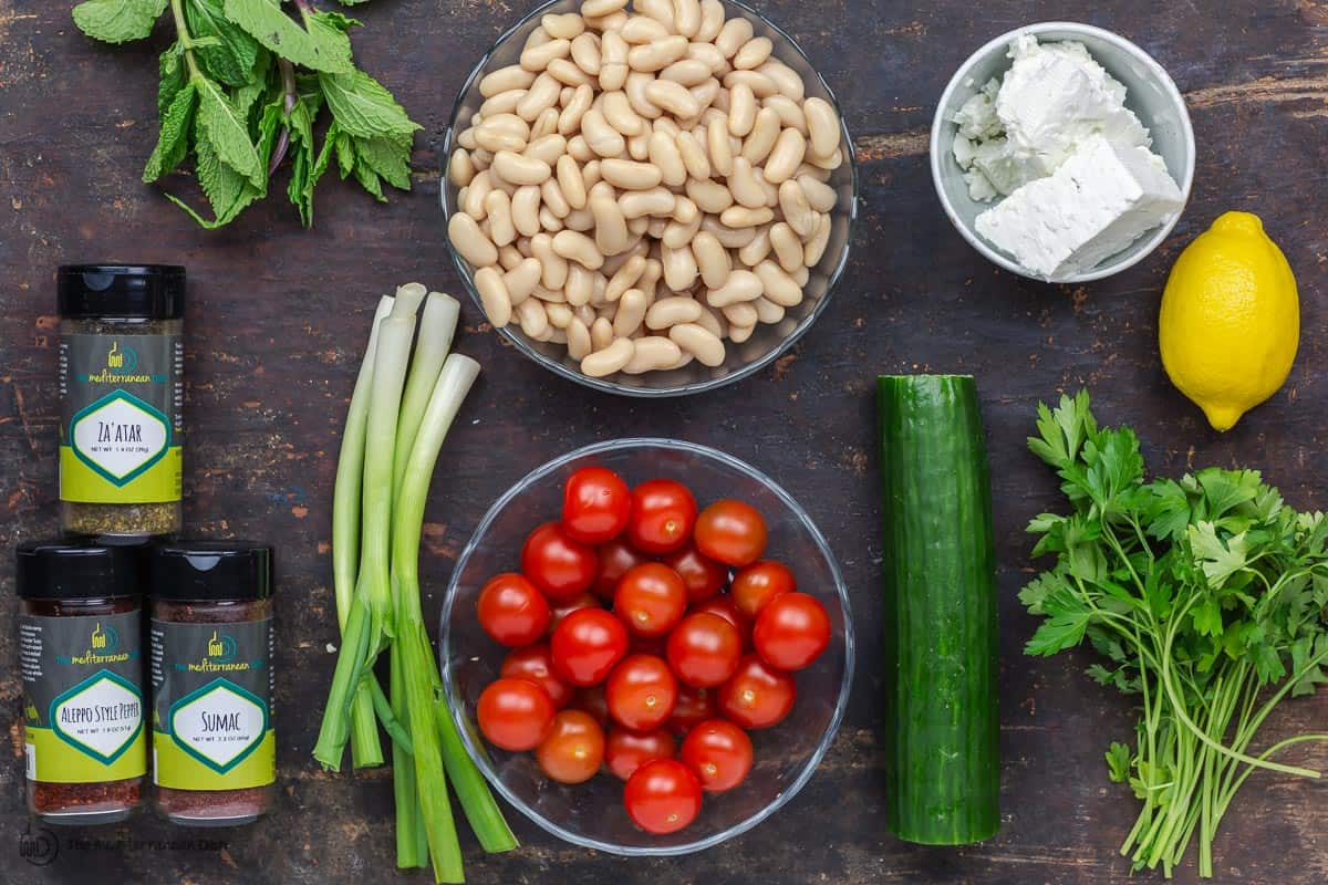 Ingredients for white bean salad. White beans, tomatoes, cucumber, green onions, herbs, spices and feta