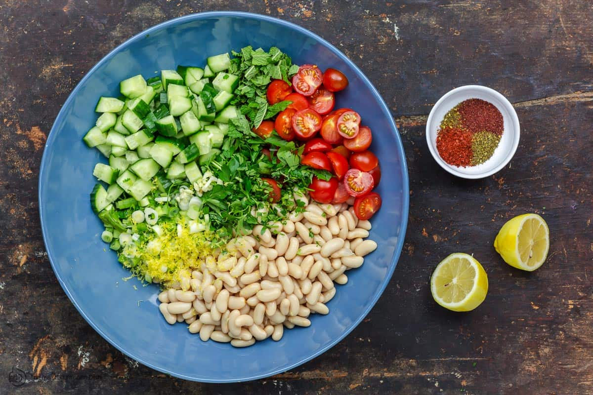 White beans, vegetables, fresh herbs in a big bowl. A small dish of spices and lemon to the side