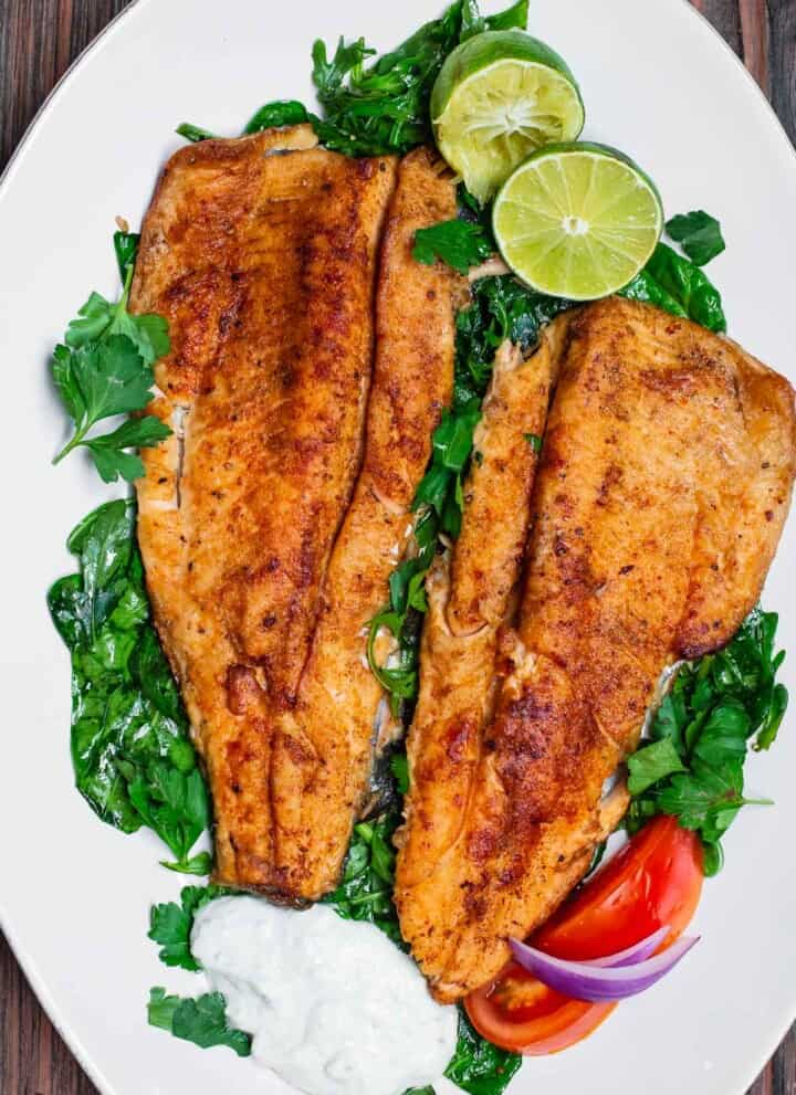pan seared trout served on a platter of greens with tzatziki sauce and limes
