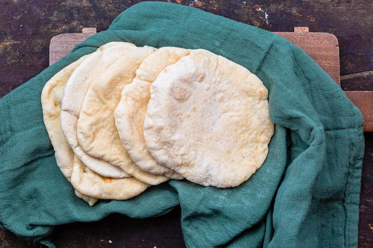 baked pita loaves on a kitchen towel