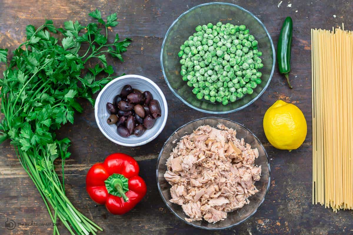 ingredients for tuna pasta. spaghetti, tuna, lemon, frozen peas, bell pepper, olives, parsley and jalapeno