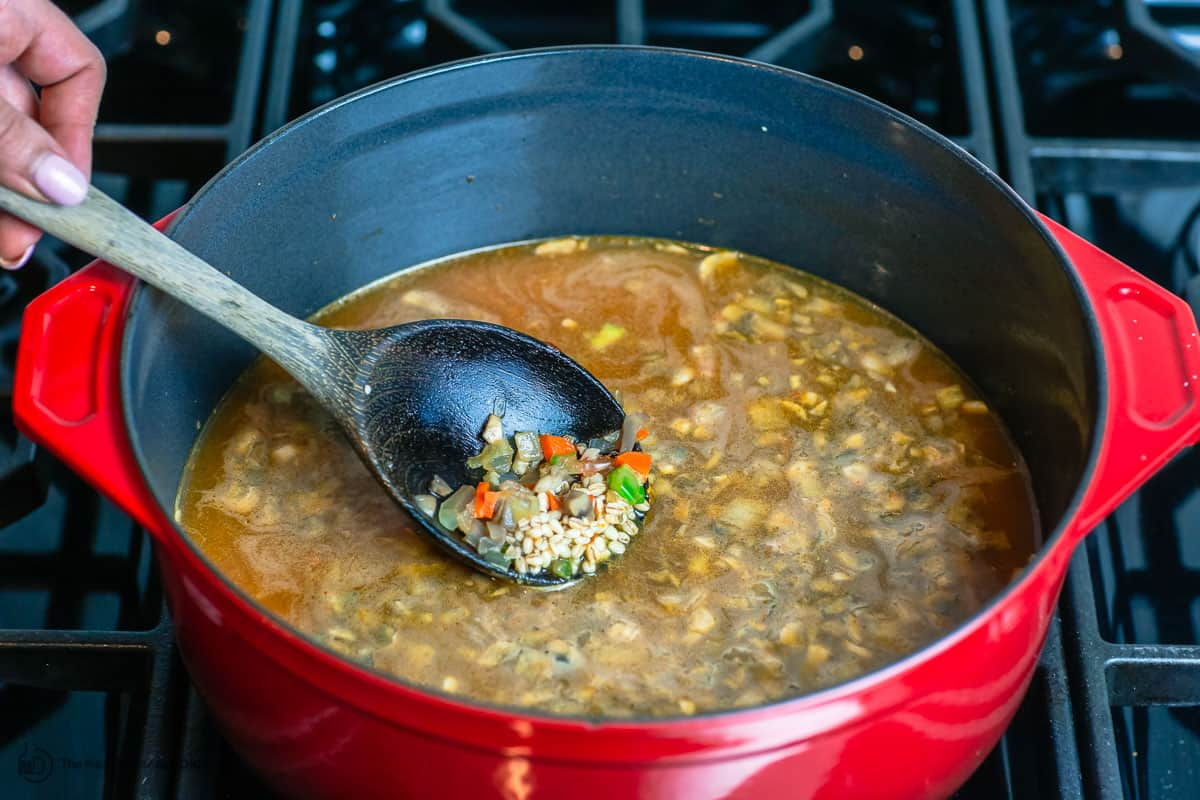 broth and barley are added to the pot