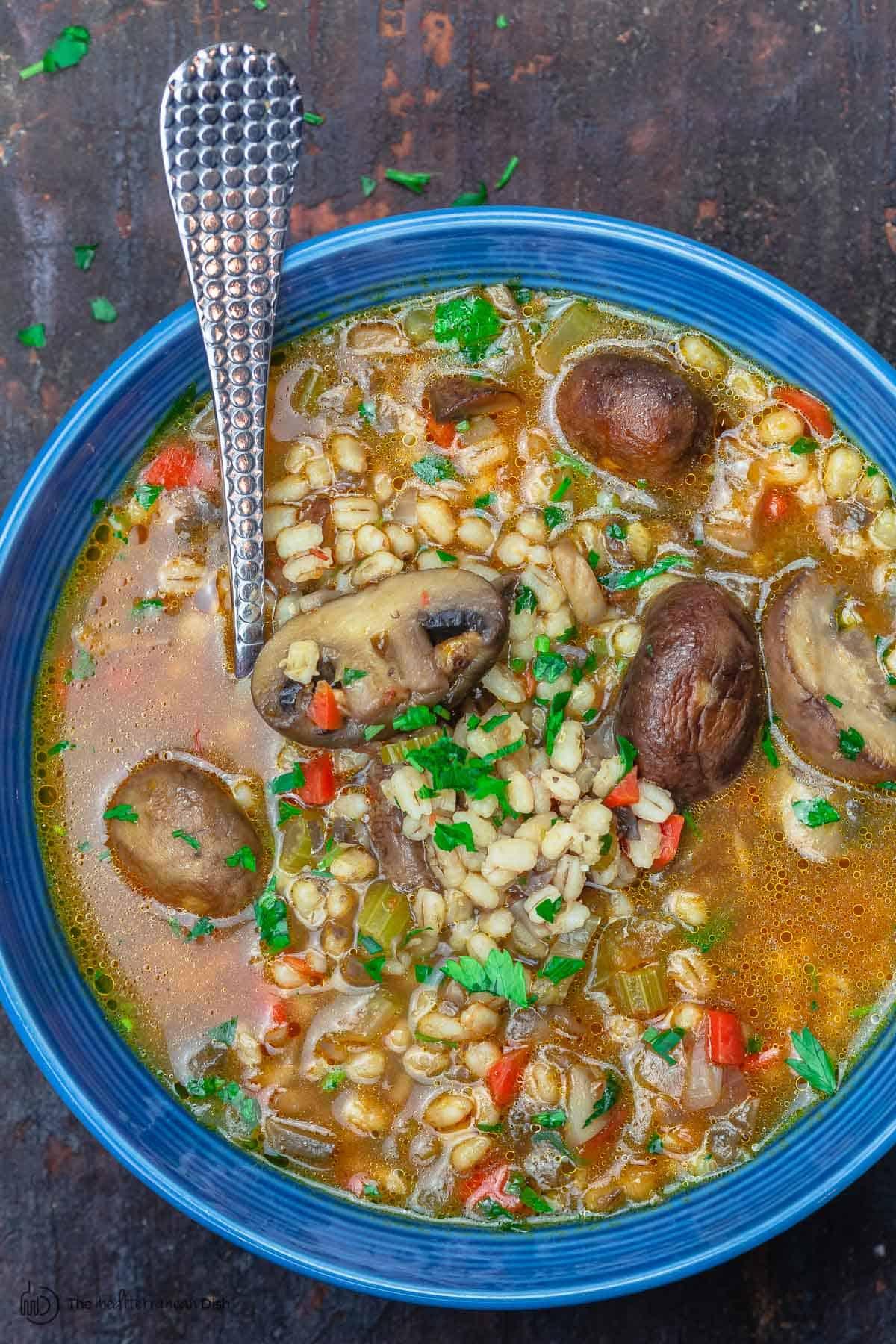 Mushroom barley soup served in a blue dinner bowl