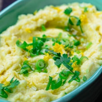 Skordalia greek garlic mashed potato dip in serving bowl with scallions and parsley for garnish