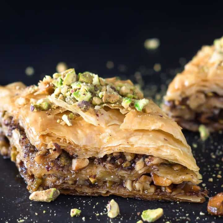 Two pieces of Greek baklava with pistachio pieces sprinkled on top