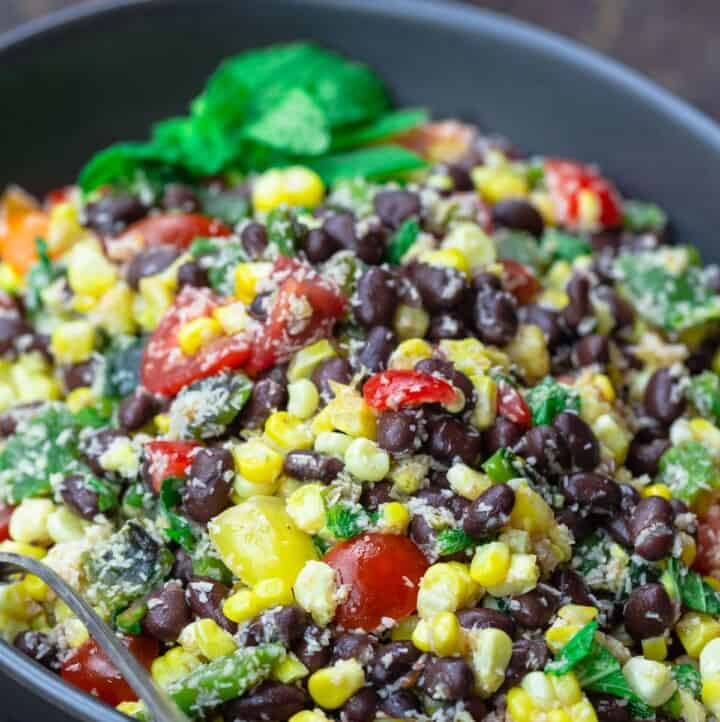Black bean and corn salad with mint garnish. limes to the side