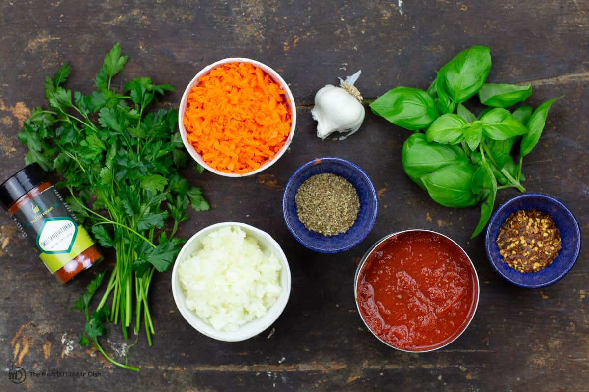 Ingredients for homemade spaghetti sauce: onions, garlic, carrots, canned crushed tomatoes, spices, and fresh herbs