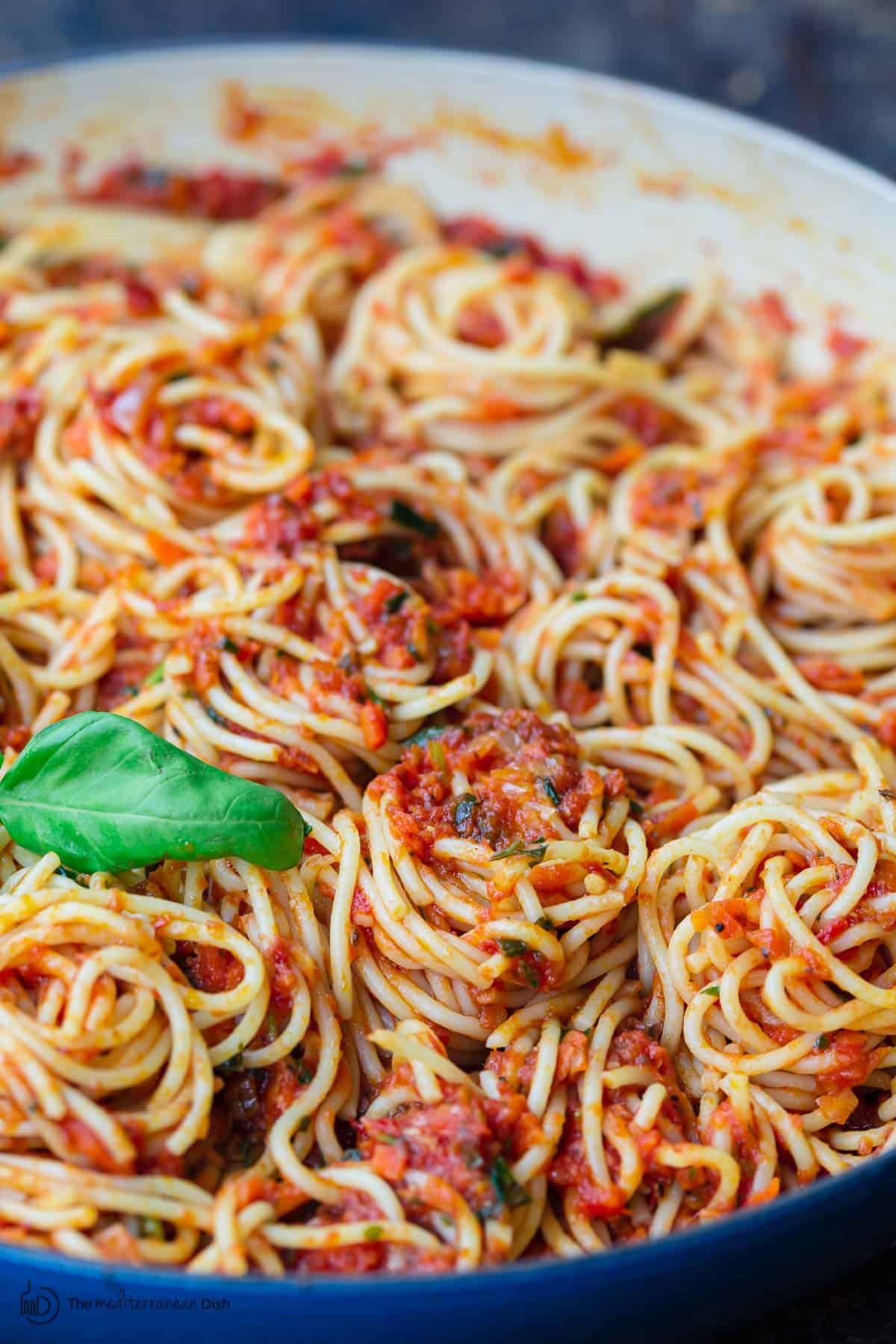 Spaghetti covered in sauce and garnished with fresh basil