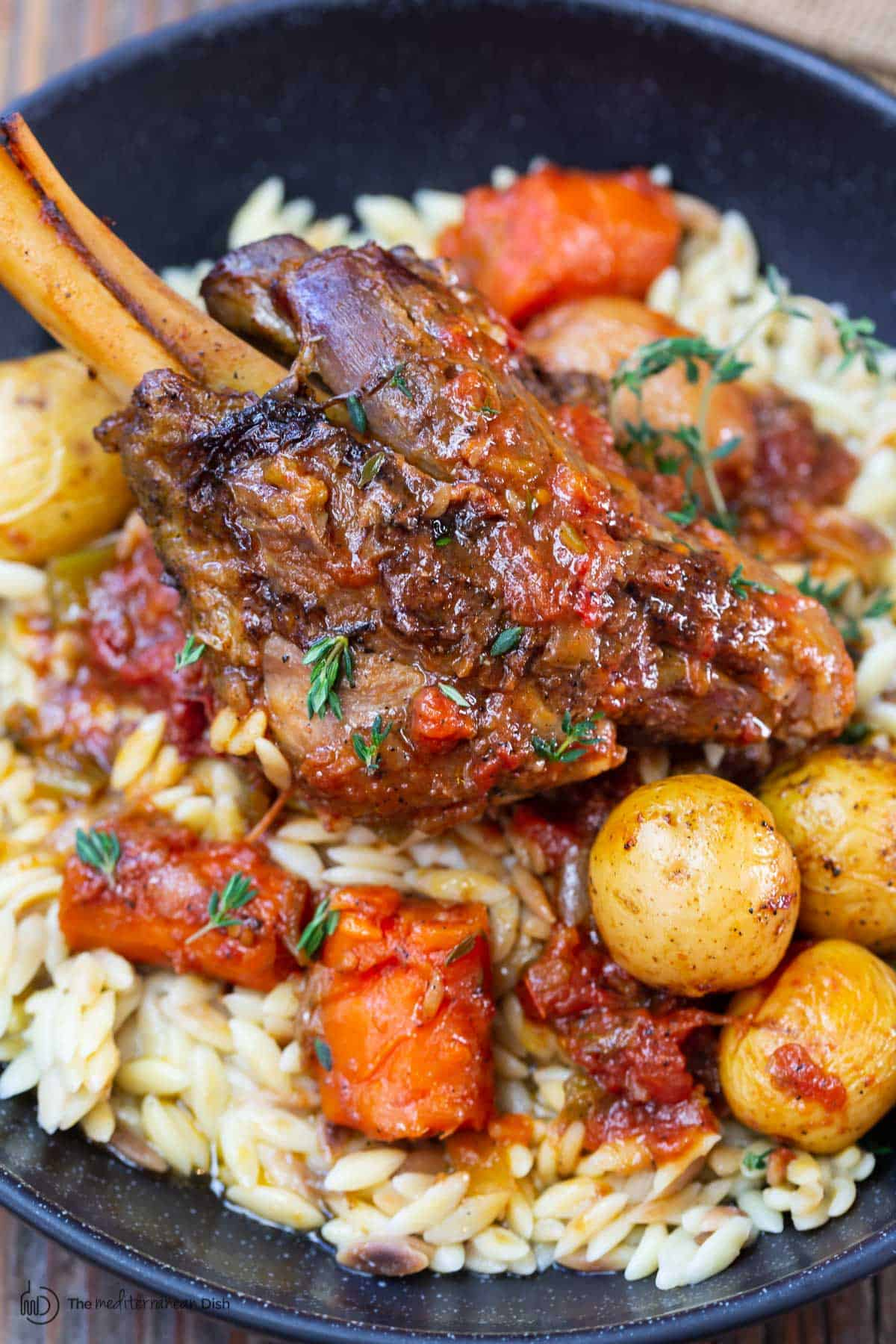 one lamb shank served with vegetables and orzo