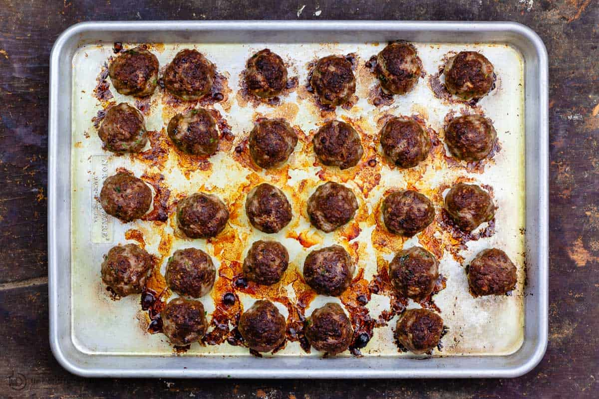 Broiled meatballs on a baking sheet